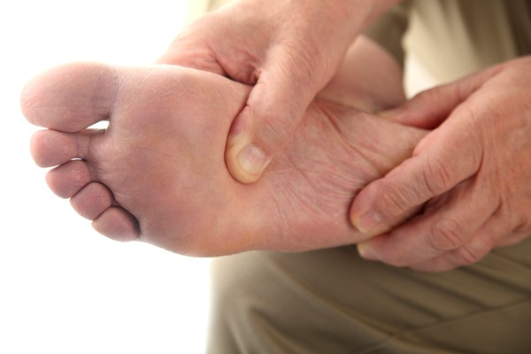 person holding his foot in pain